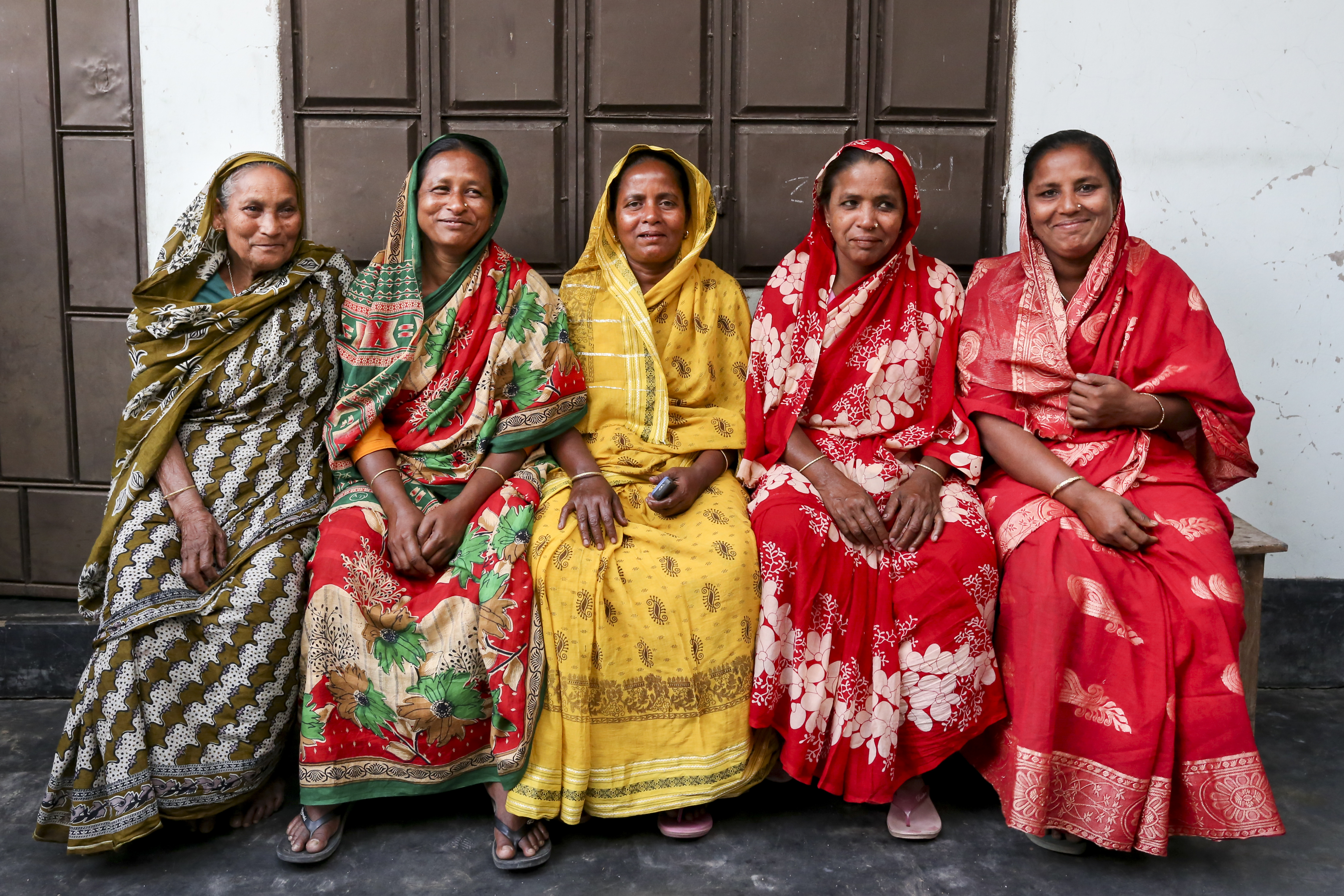 5 women sit together proudly looking into the camera